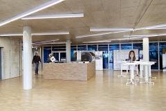 Elma Schmidbauer Neubau Erweiterungsbau, Transparenz prägt auch den großzügigen Eingangsbereich bei Elma Schmidbauer. Farbige Glaswände eröffnen Besuchern den Blick in dei Produktionshalle.
