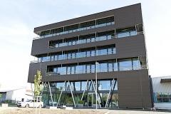 Elma Schmidbauer Neubau Erweiterungsbau, Die Fassade des fünfstöckigen Neubaus mäandriert gegen den Himmel als Sinnbild für die Expansion bei Elma Schmidbauer.